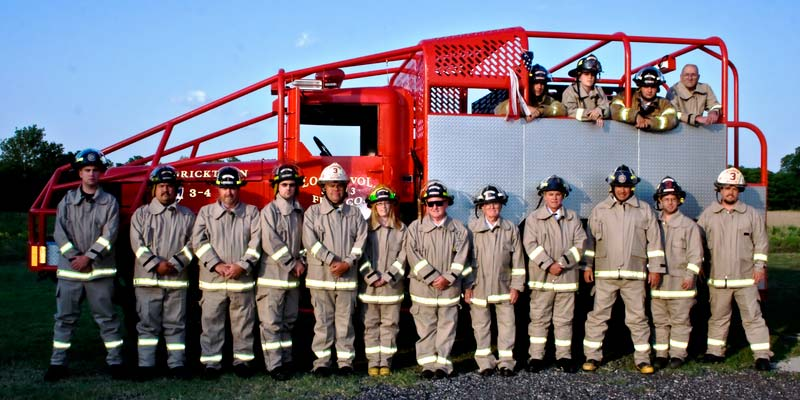 Volunteer firefighters in full gear lined up in front of a truck