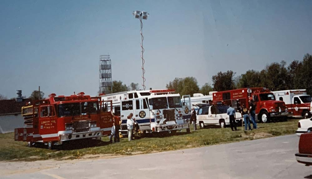 Row of emergency vehicles parked on grass