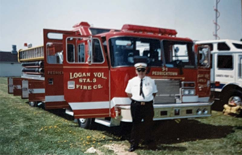 Chief stands in front of firetruck