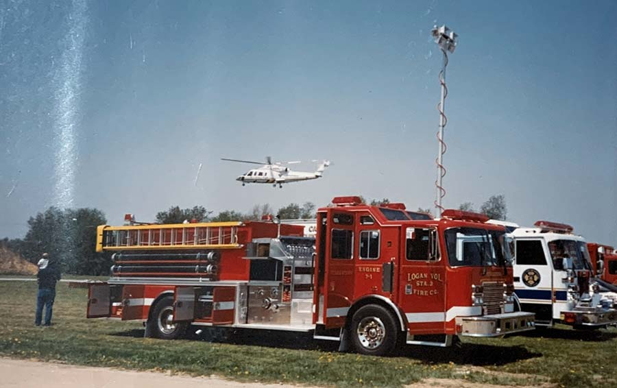 Firetruck with helicopter hovering in backgroiund