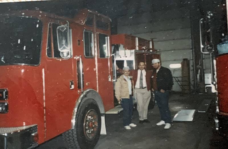 Three men standing alongside firetruck