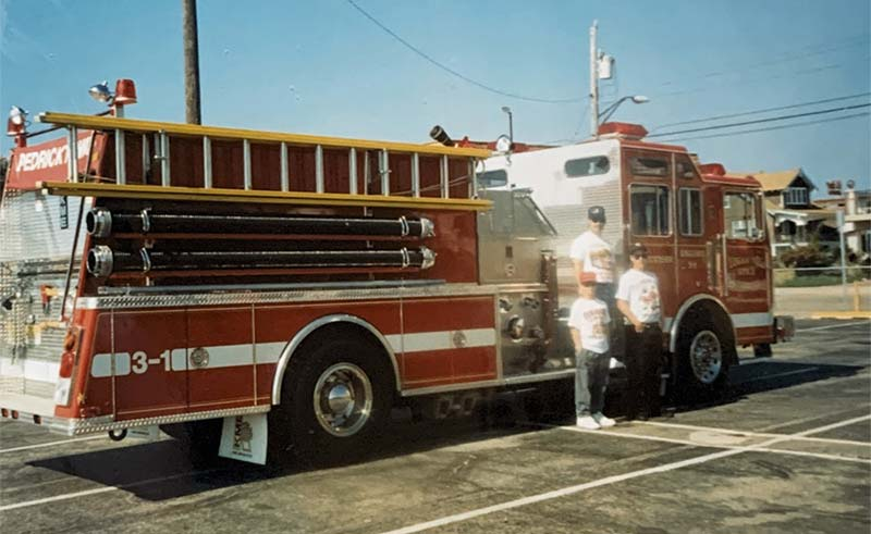 Man and two kids standing next to firetruck