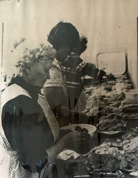 Women standing at table filled with food