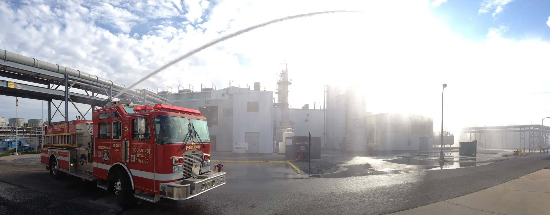 Firetruck hosing down an industrial area with arc of water