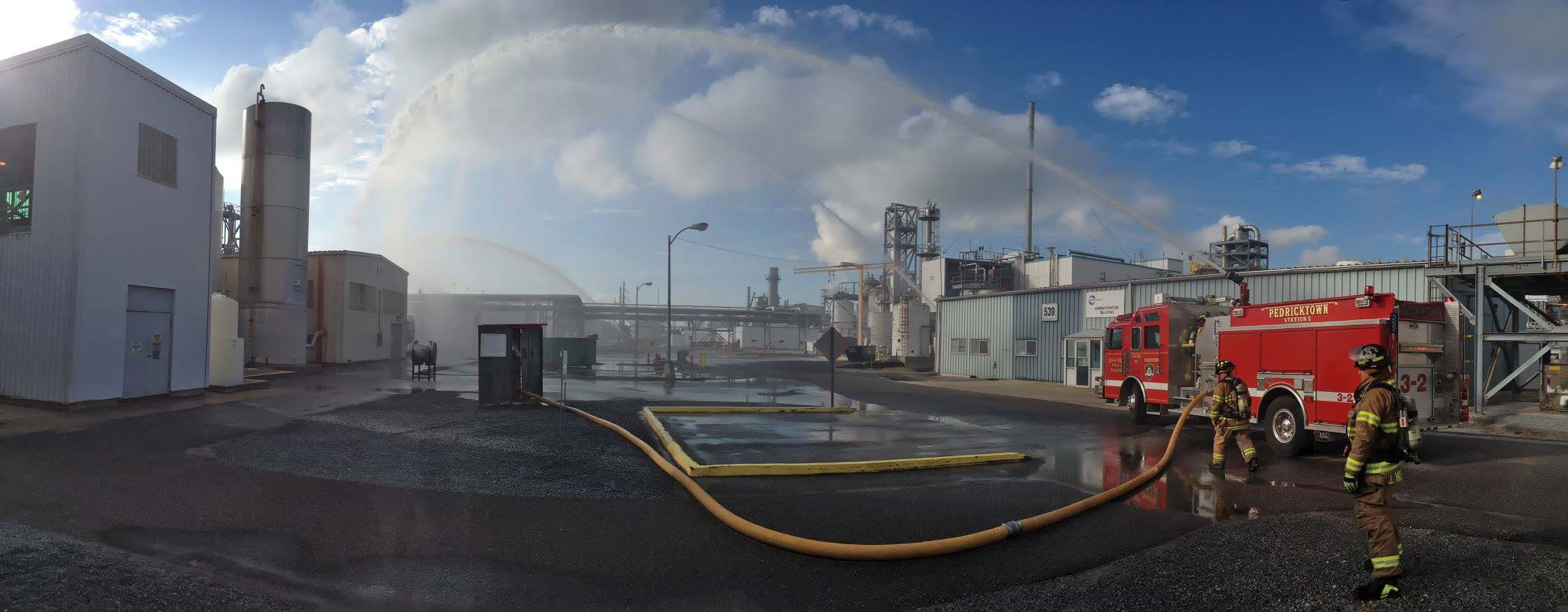 Panoramic image of fire fighters working in an industrial area