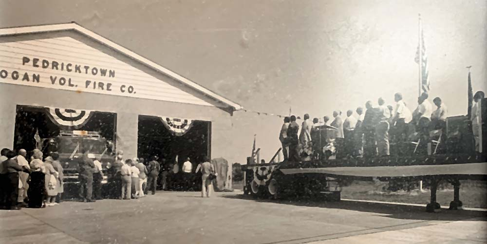 Black and white photo with people on stage in front of firehouse