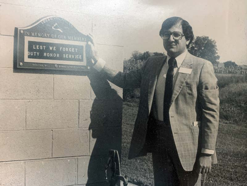 Man standing in front of new building plaque