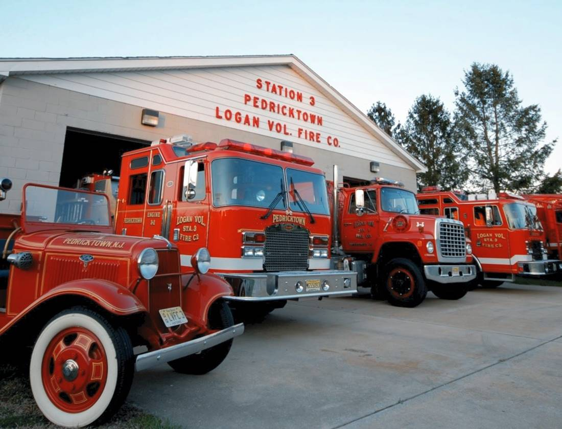 Vehicles in front of firehouse including antique truck