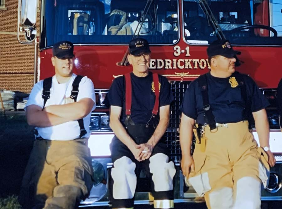 Three firefighers sitting on front bumper of truck