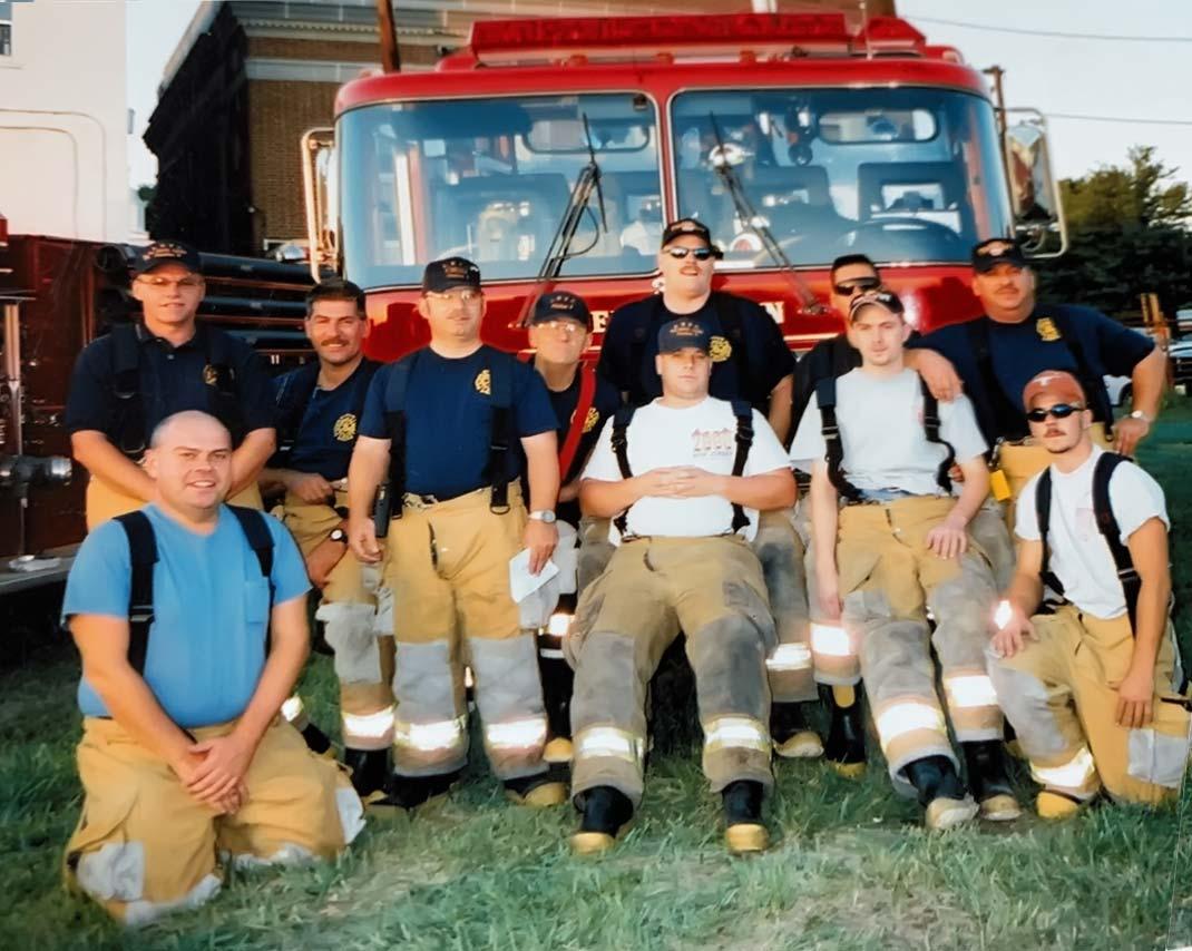 Firefighters in firepants posing in front of truck