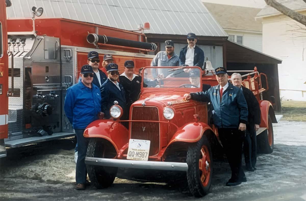Volunteers standing around vintage firetruck